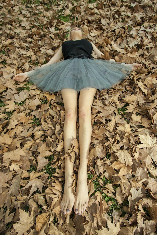 woman in black dress lying on dried leaves