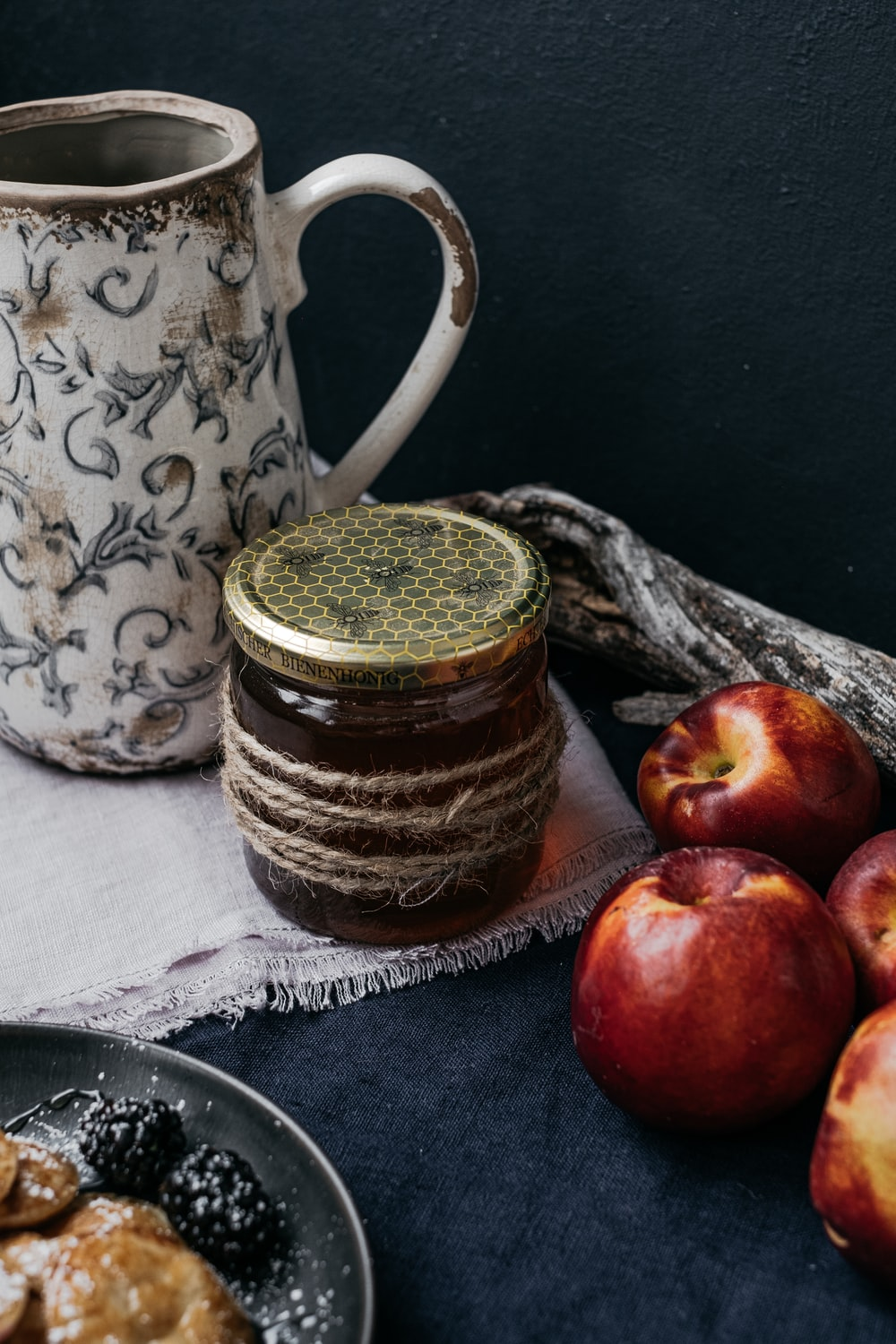 red apples beside brown and white ceramic jar