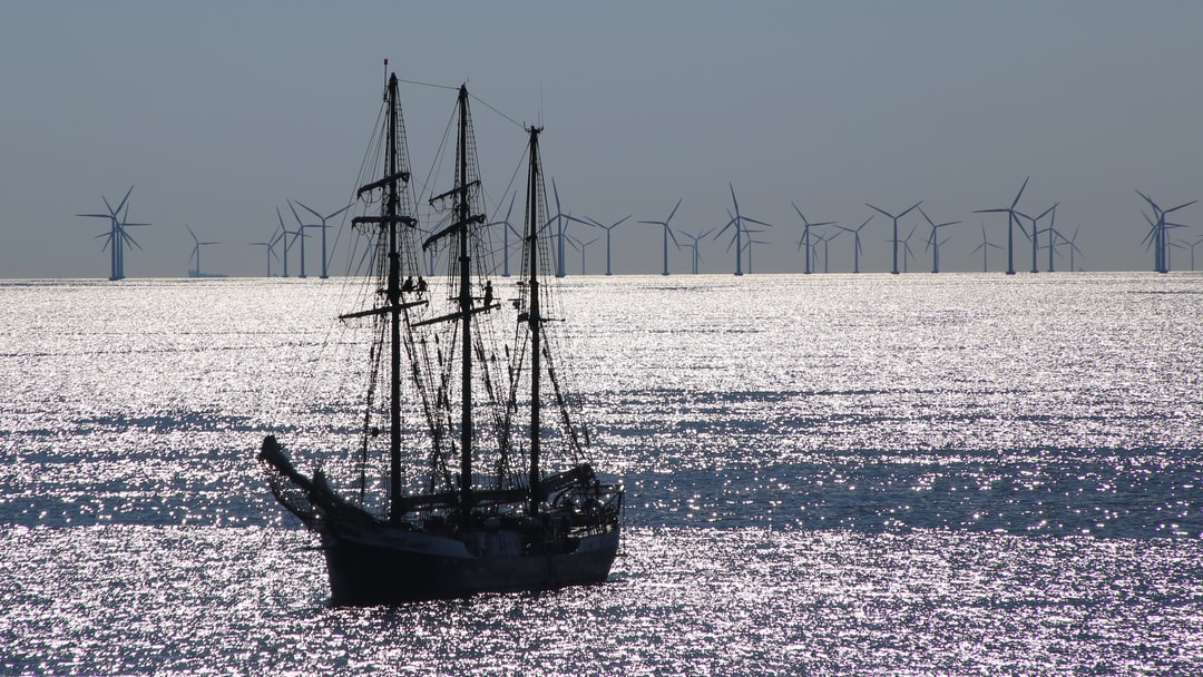 Two eras of using wind energy in one photo: Sailing ship Fridtjof Nansen (built 1919) in front of a modern offshore wind park close to Danish port of Gedser.  Using wind to create energy, mobility and transportation is long known. Today it gets a revival in creating renewable energy to protect our climate.  Link to ship: https://de.wikipedia.org/wiki/Fridtjof_Nansen_(Schiff,_1919)