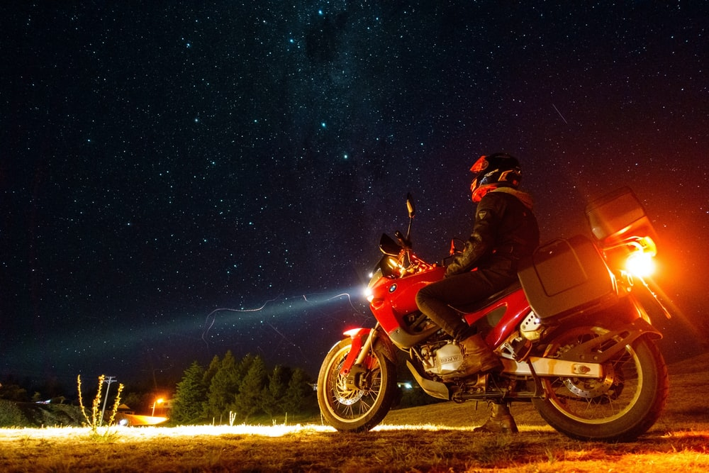 man in red and black motorcycle suit riding on red motorcycle under starry night
