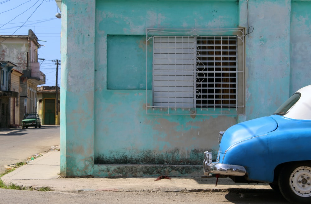 blue and white motor scooter parked beside blue concrete building