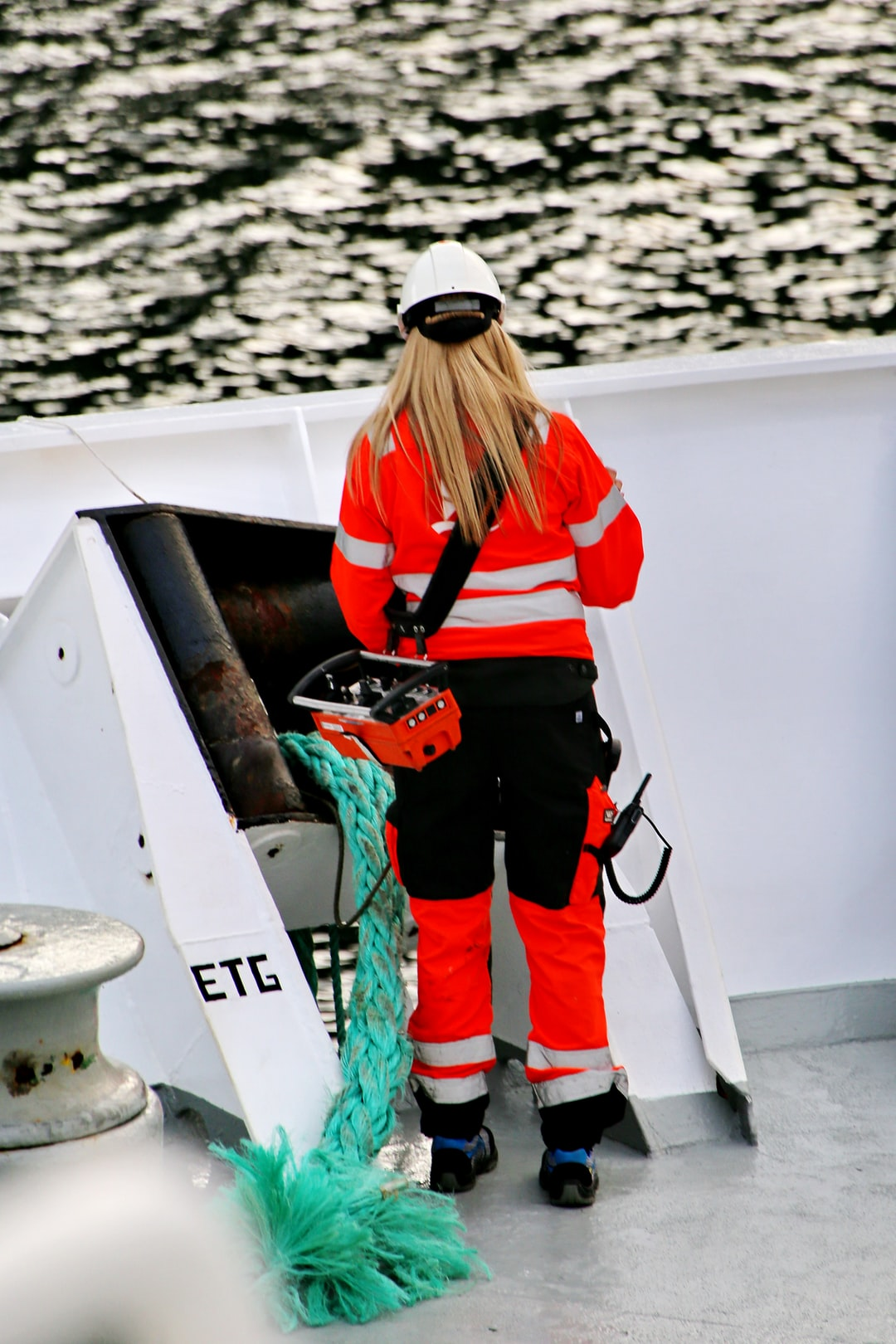 A woman working on deck of a coastal transport vessel in polar region of Norway; same job as for male colleagues on a big ship with heavy weather and equipment.  Equal job = equal pay.