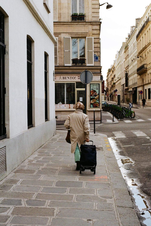 woman in beige coat sitting on sidewalk during daytime