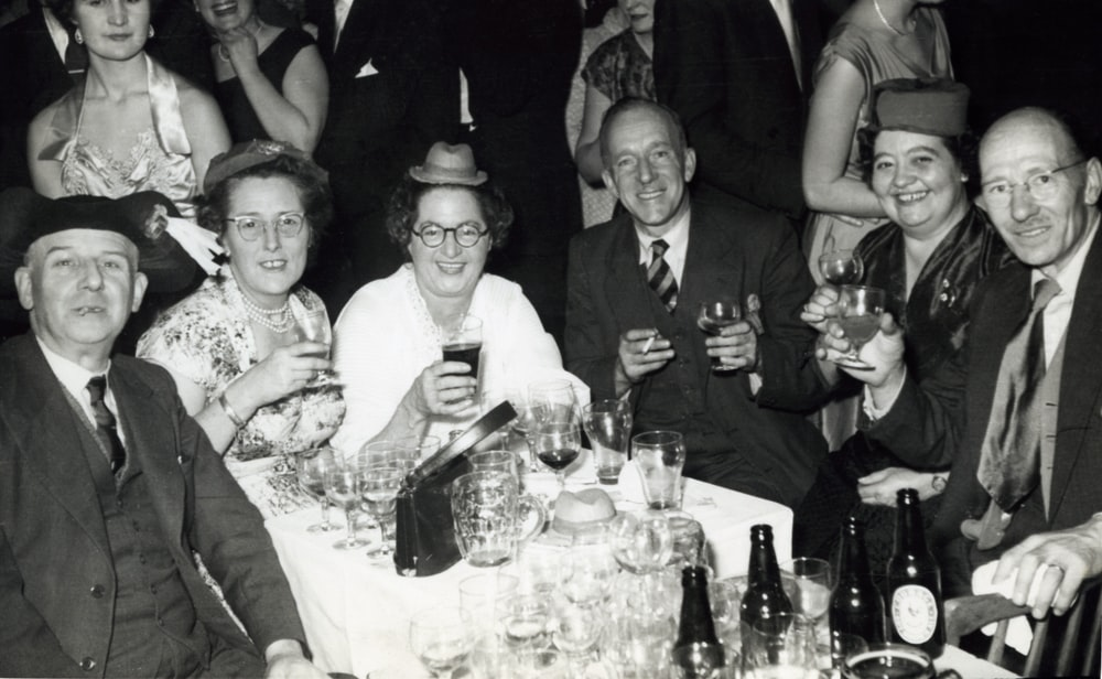 grayscale photo of group of people in front of table with drinking glasses