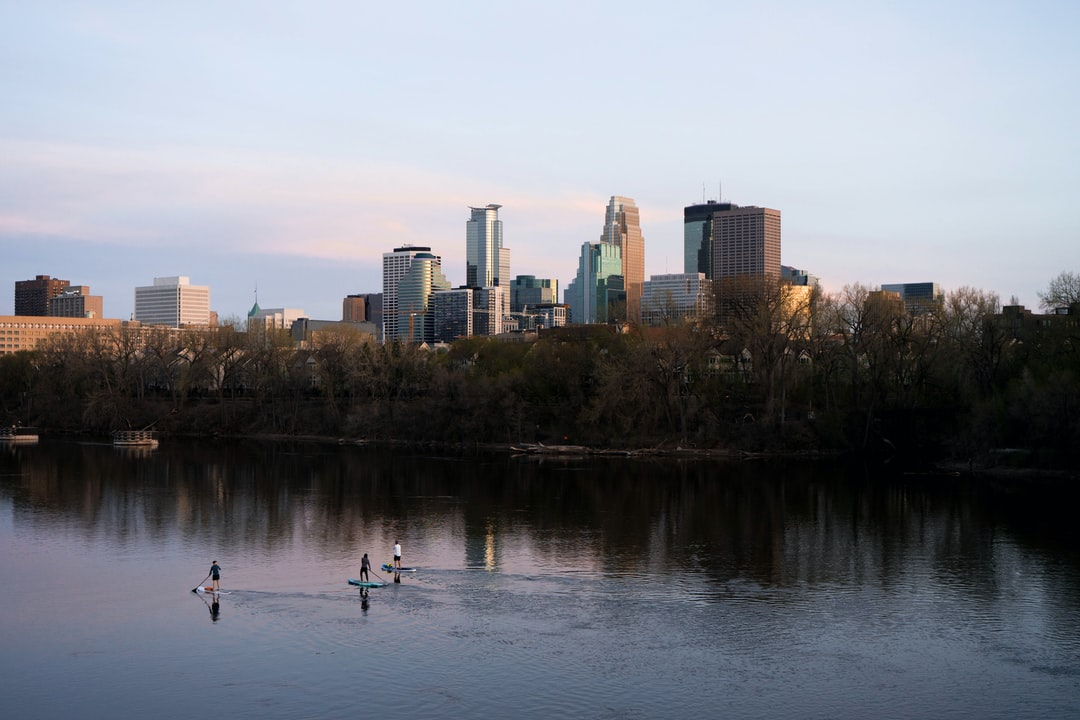 Minneapolis skyline with a few paddle boarders going down the Mississippi River.