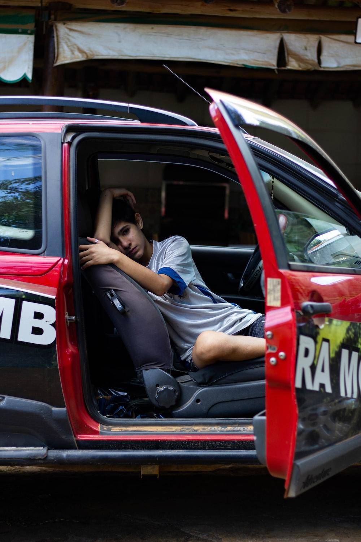man in blue t-shirt sitting on car seat