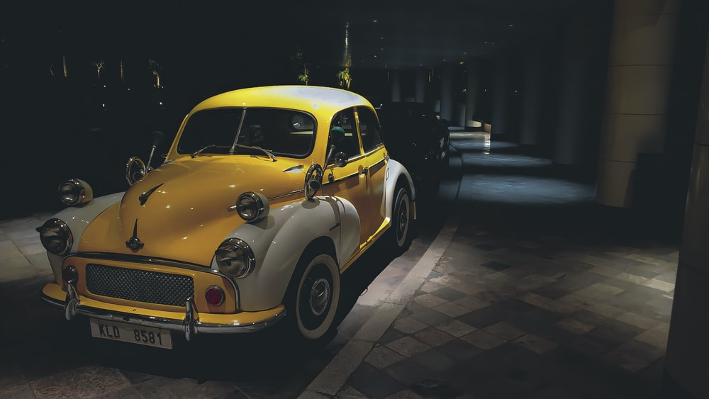yellow volkswagen beetle parked on sidewalk during night time