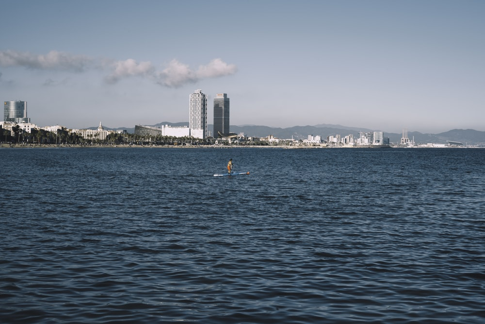 people swimming on sea near city buildings during daytime