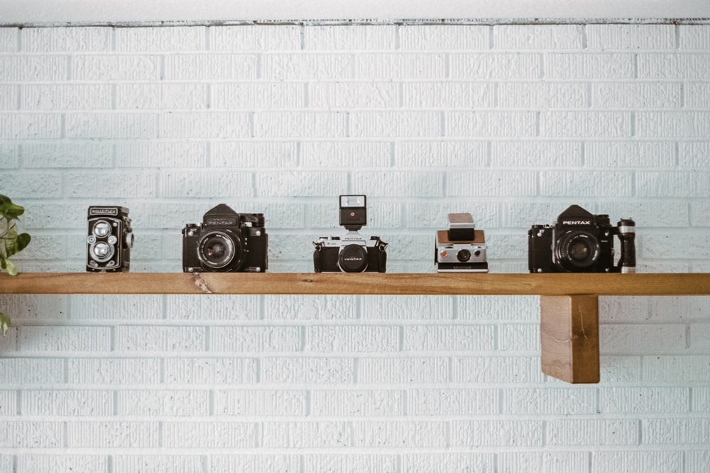 black and silver camera on brown wooden wall rack
