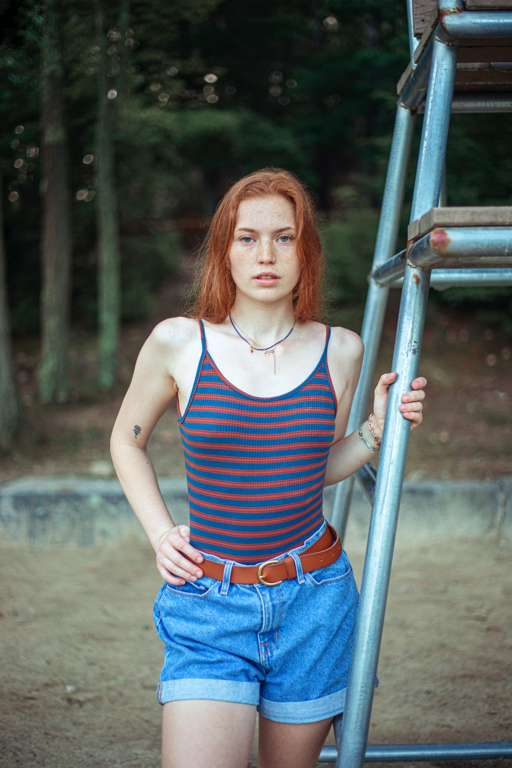 woman in blue and white stripe tank top and blue denim jeans standing beside gray metal