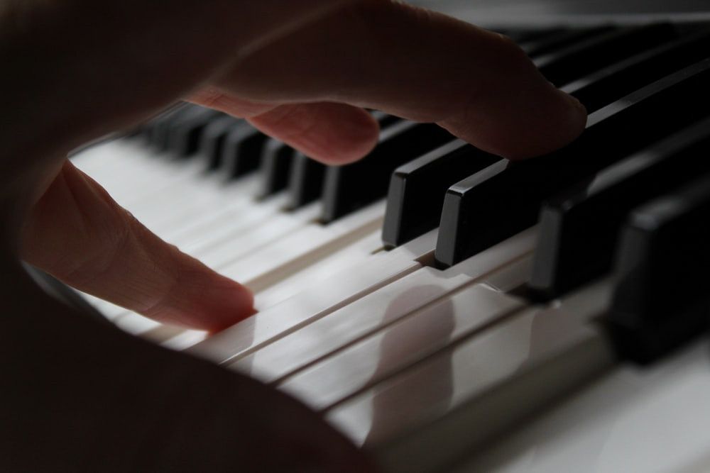 persons hand on piano keys