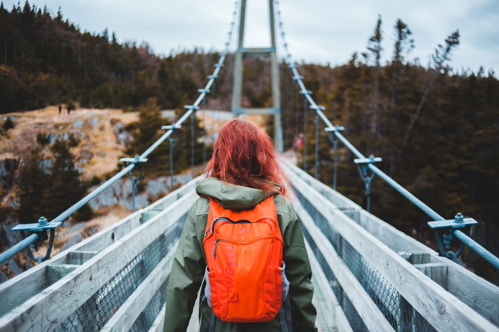 woman in orange jacket and blue denim jeans standing on bridge during daytime
