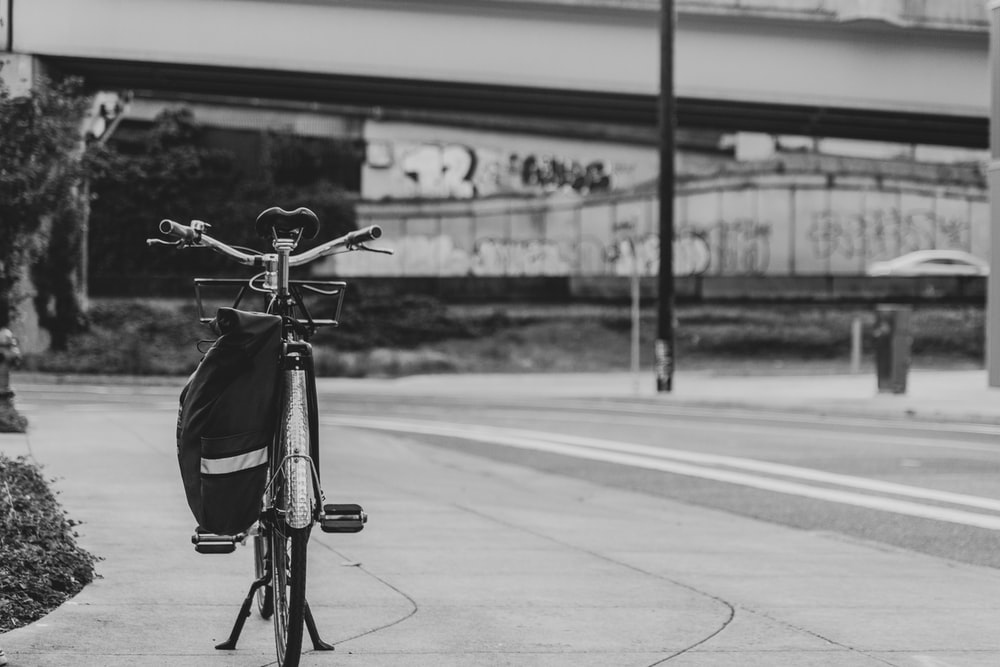 grayscale photo of a bicycle on a road