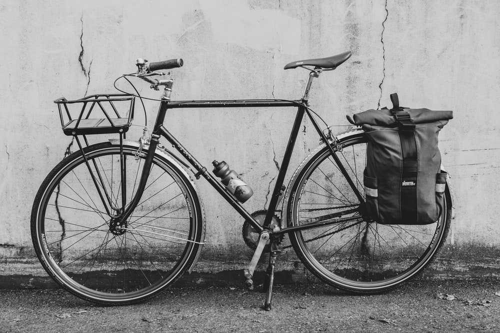 grayscale photo of bicycle leaning on wall