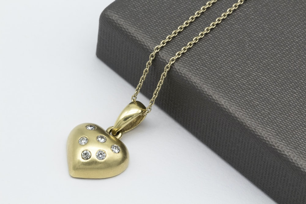 gold heart pendant necklace beside gray leather pouch