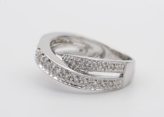 silver diamond ring on white surface