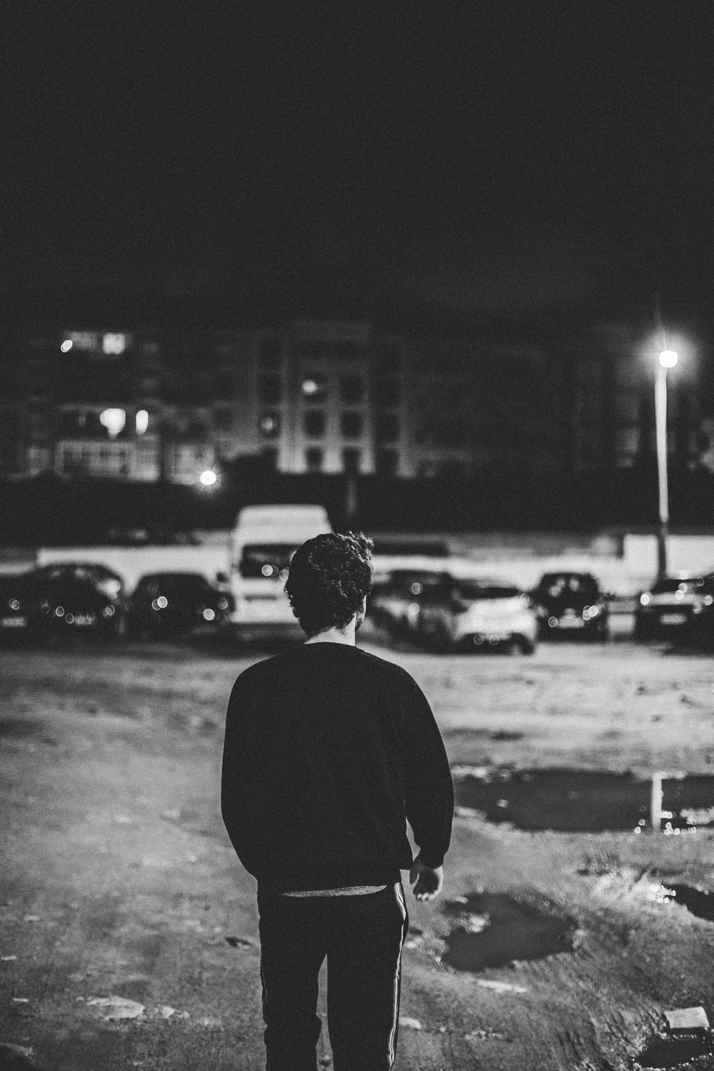 man in black long sleeve shirt standing on road during night time