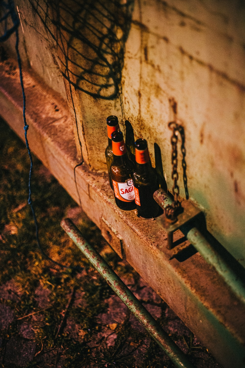 3 brown glass bottles on brown concrete wall