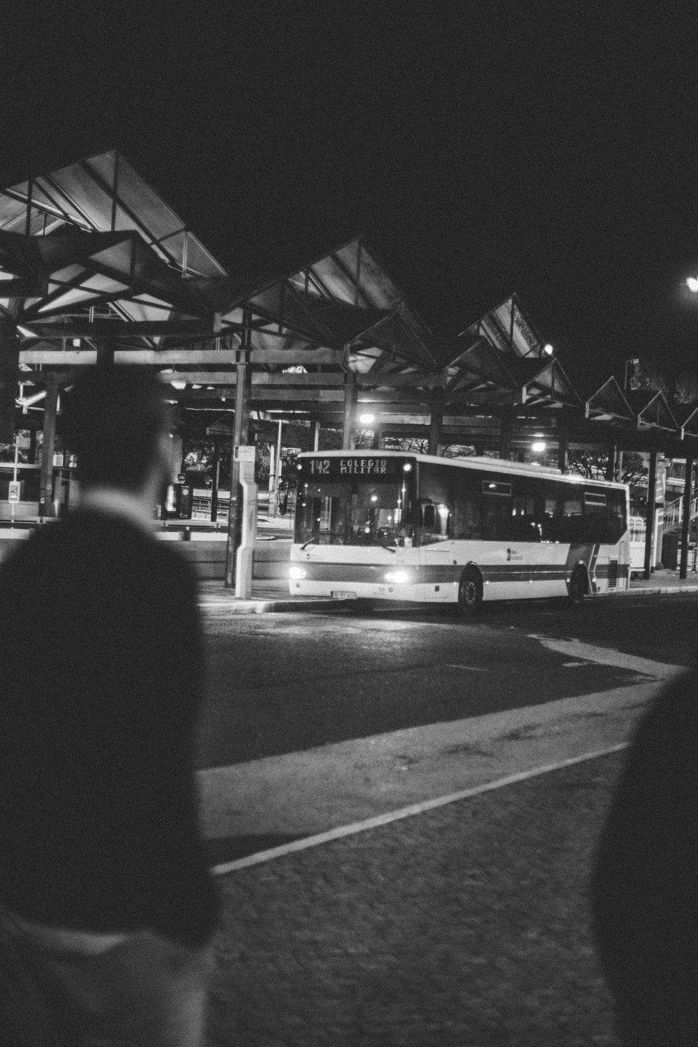 grayscale photo of man in black jacket standing near bus