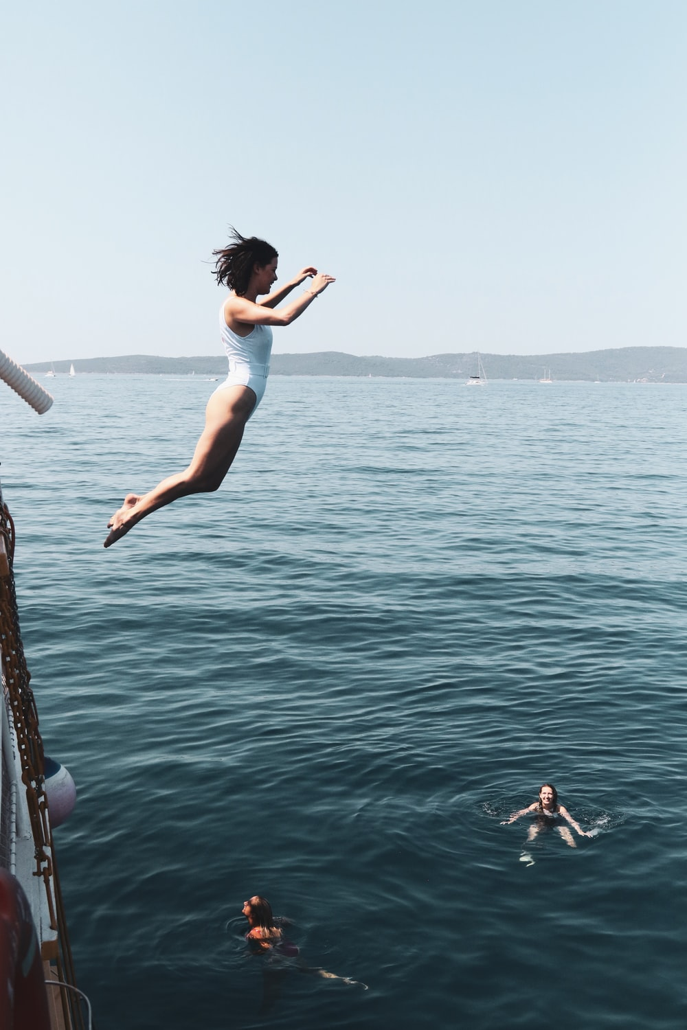 woman in white tank top and white shorts jumping on water during daytime
