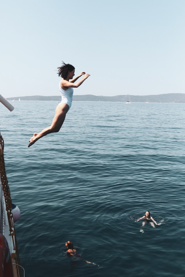 A lady jumping into the sea