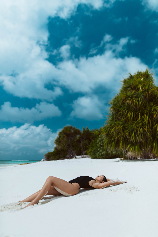 woman in black bikini lying on white sand beach during daytime
