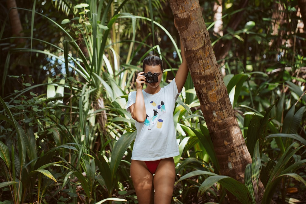 woman in white and blue floral shirt and white shorts standing beside green palm tree during
