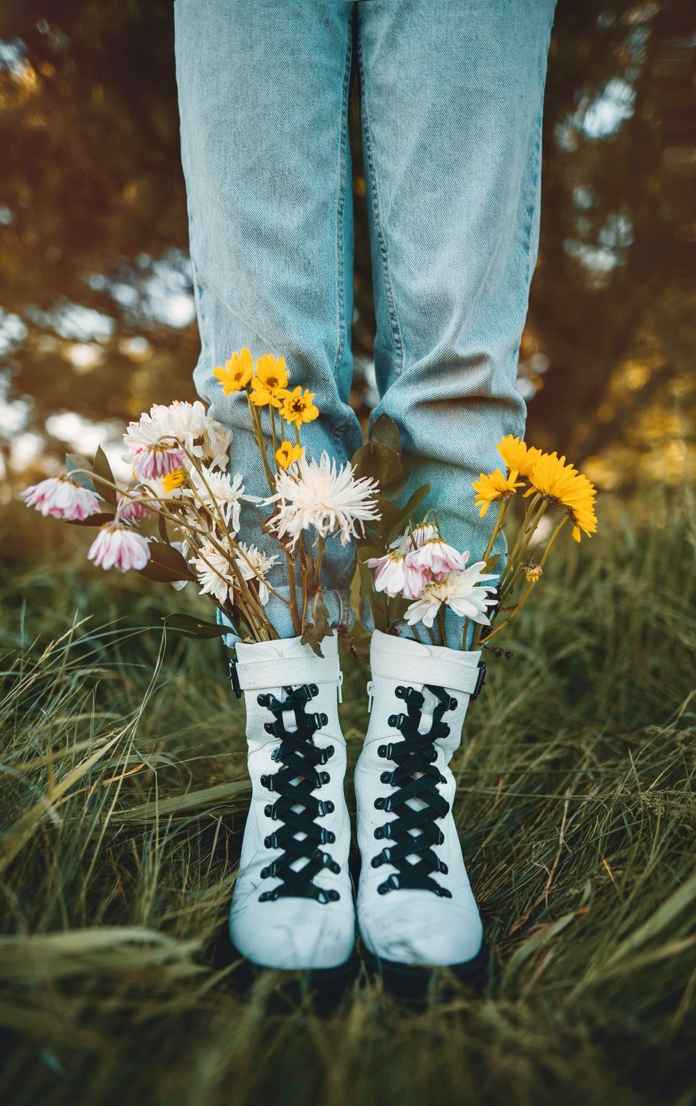 person in blue denim jeans and white and black boots holding white and yellow flowers