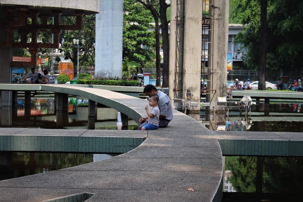 man in blue denim jacket sitting on gray concrete bench during daytime