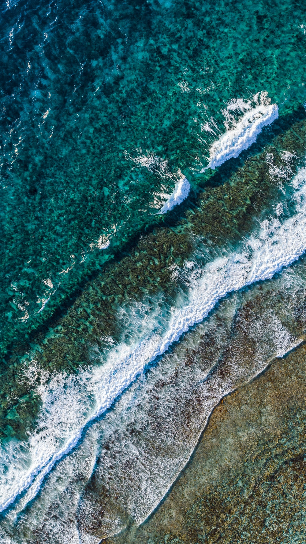 aerial view of green and white ocean waves during daytime