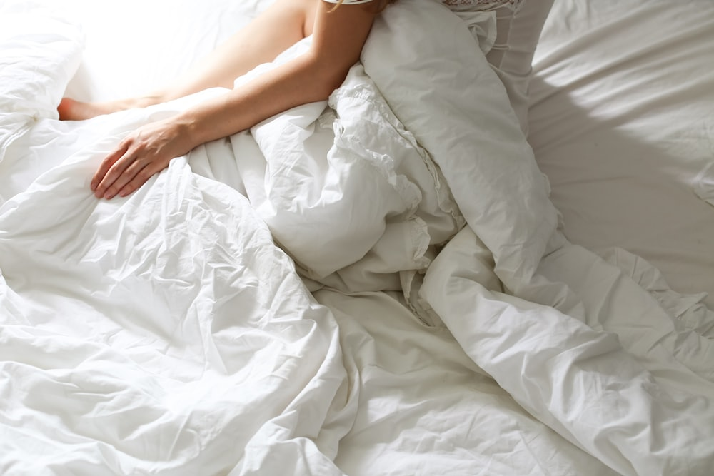 woman lying on white bed