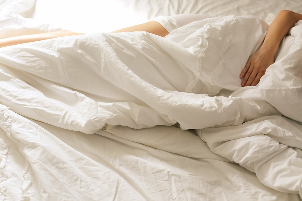 person lying on bed covered with white blanket