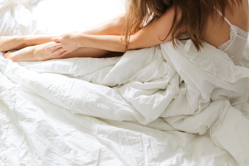 topless woman lying on bed covered with white blanket