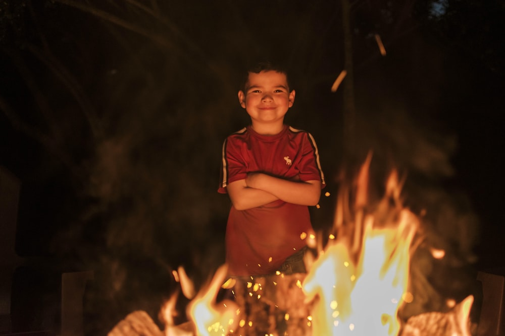 boy in red polo shirt holding lighted sparkler