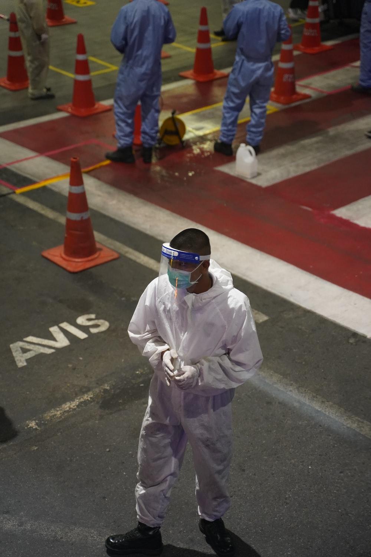 man in white long sleeve shirt wearing white helmet standing on gray concrete floor