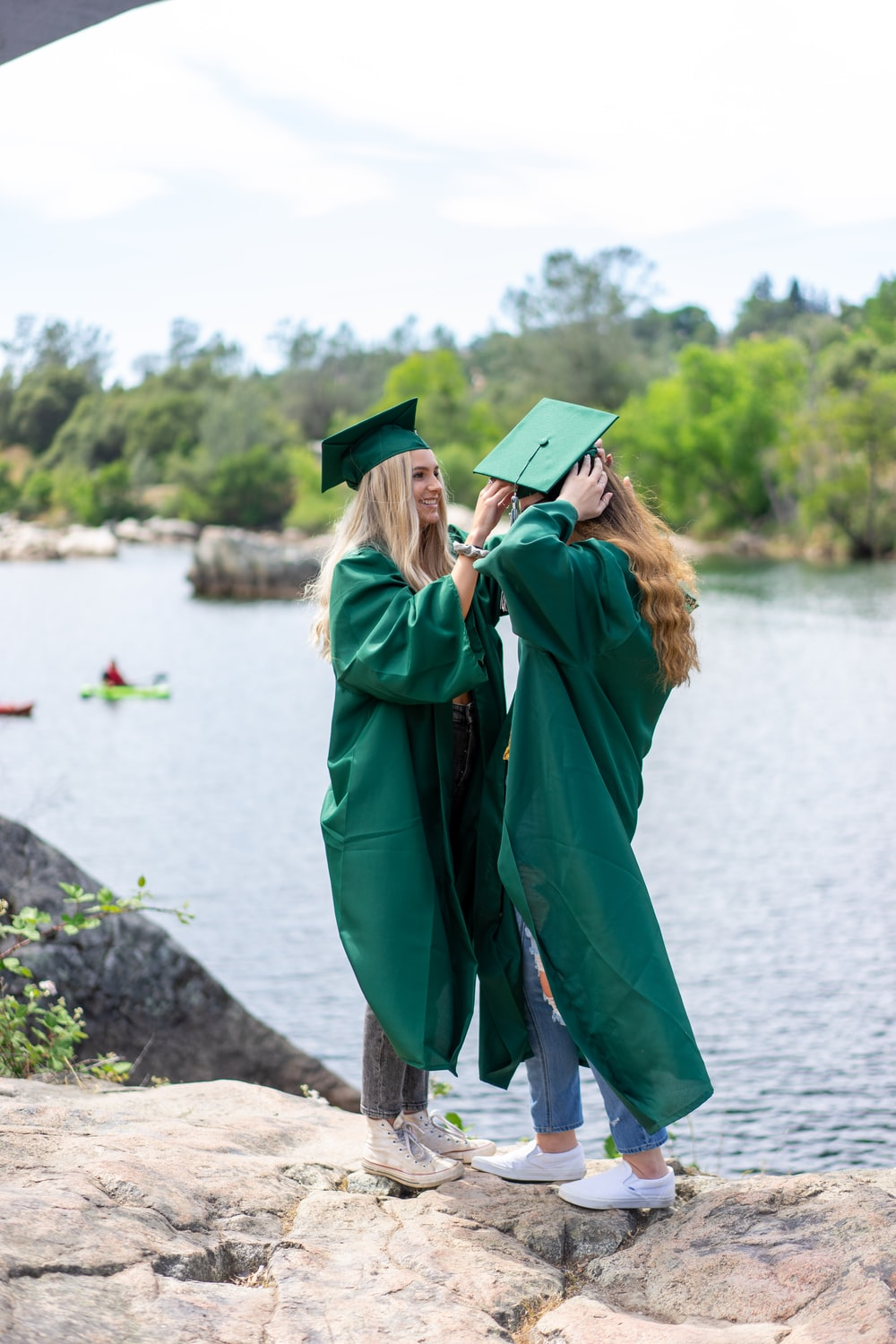 woman in green academic dress and black mortar board standing on brown wooden log during daytime