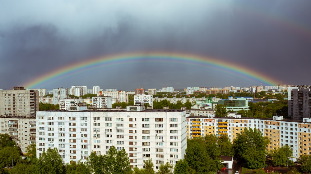 rainbow over city with green trees and buildings during daytime