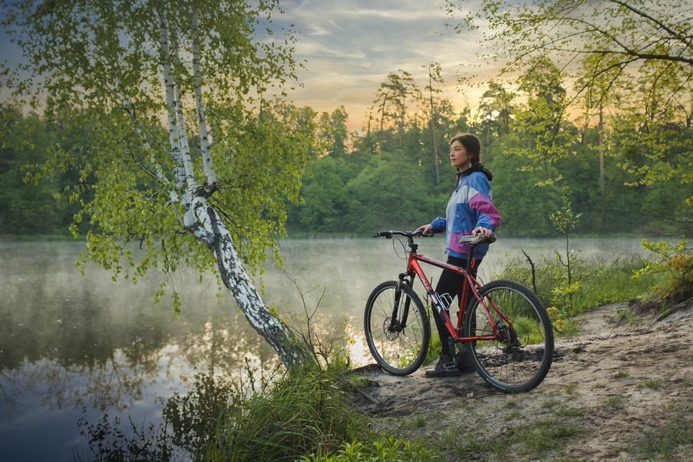 woman in blue shirt riding red and black mountain bike on river during daytime