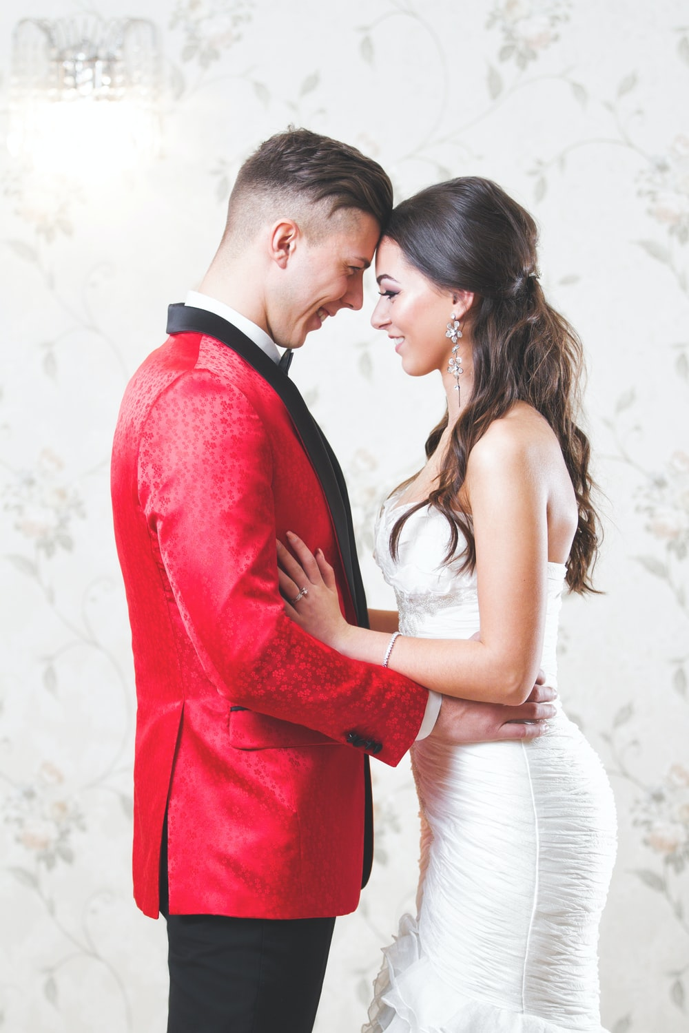 man in red suit kissing woman in white dress
