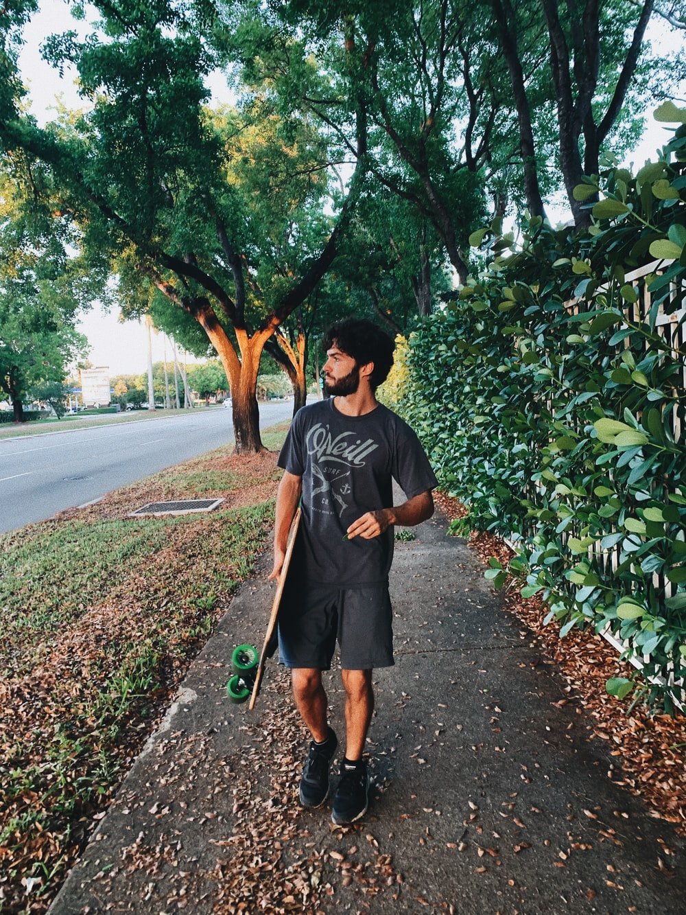 man in black crew neck t-shirt standing on road during daytime