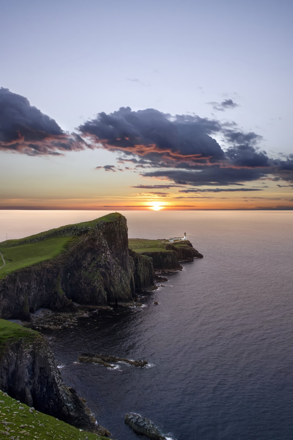 green and black mountain beside sea during sunset