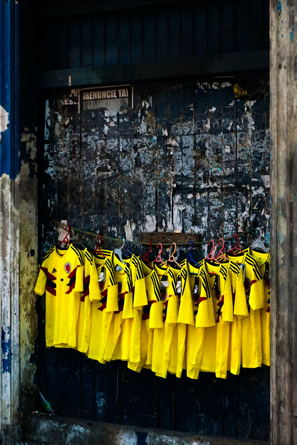 group of men in yellow and black long sleeve shirt standing beside brown concrete wall