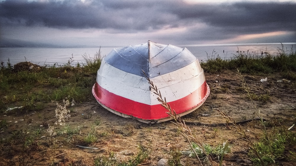 white and red boat on brown grass field under white clouds during daytime