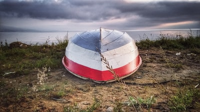 white and red boat on brown grass field under white clouds during daytime albania zoom background