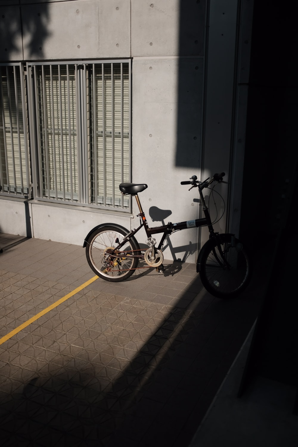 yellow and black bicycle parked beside white concrete wall