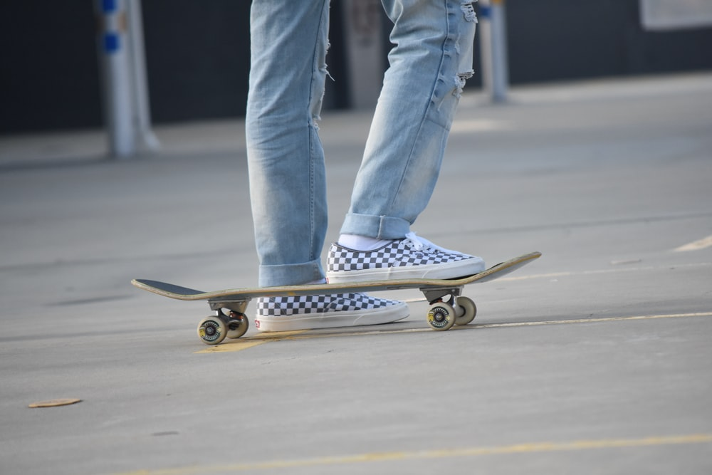 person in blue denim jeans and white sneakers riding skateboard