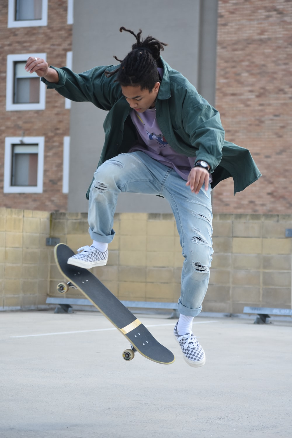 man in green hoodie and blue denim jeans sitting on skateboard during daytime
