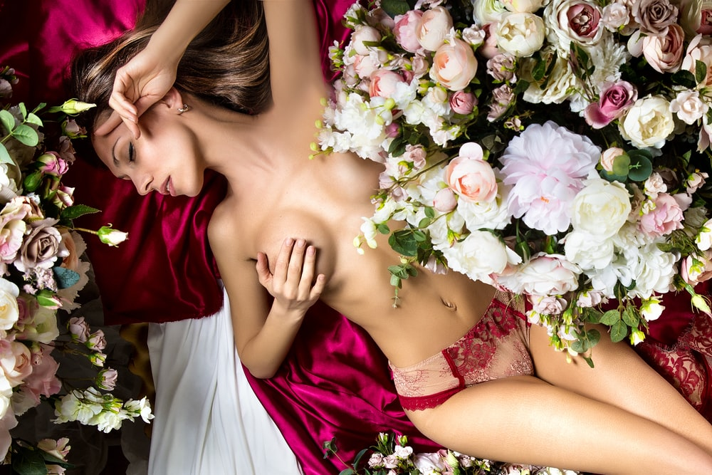 woman in red tube dress holding white and pink flowers
