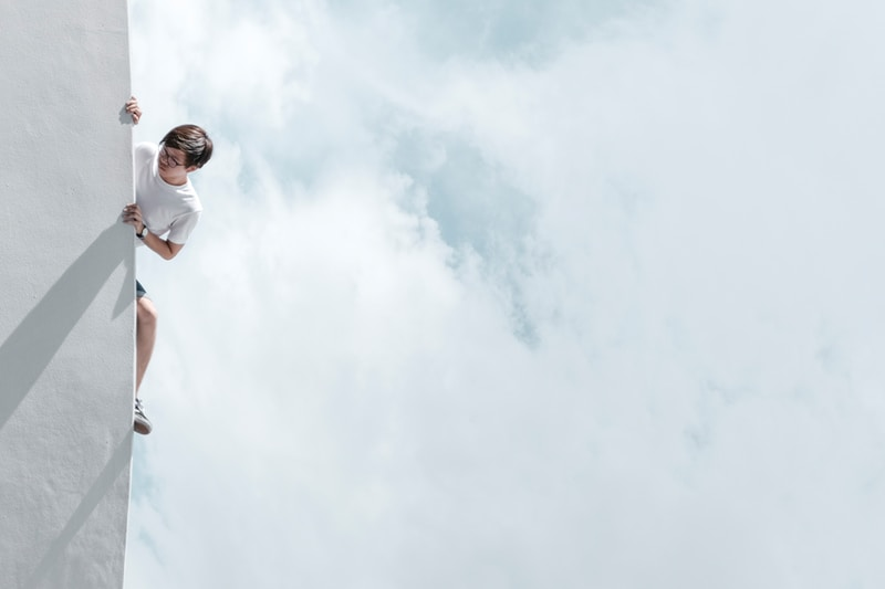 man in white t-shirt and blue denim jeans standing under white clouds during daytime