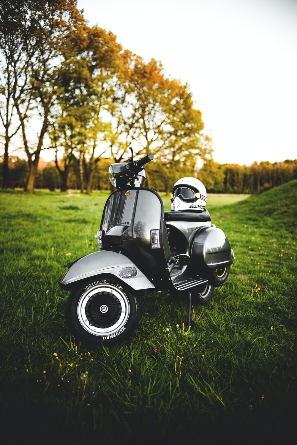 gray and black motor scooter on green grass field during daytime